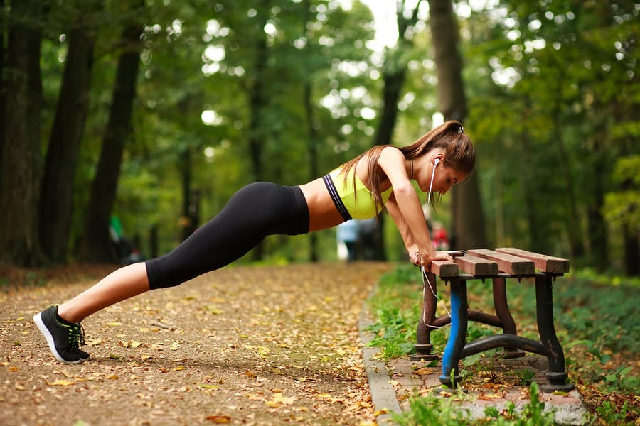 Young woman with headphones doing push ups exercises in a summer park